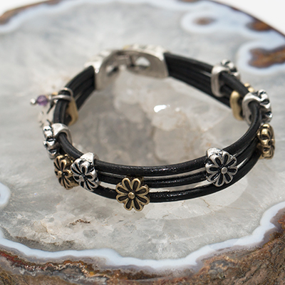 LUCKY BRAND<sup>&reg;</sup> Daisy Leather Bracelet - This bracelet features three rows of leather strands accented with antiqued gold and silver-toned flower charms.  Bracelet has silver-toned closure and measures 7.5